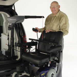 Older gentleman holding remote for Big Lifter in back of van attached to power wheelchair
