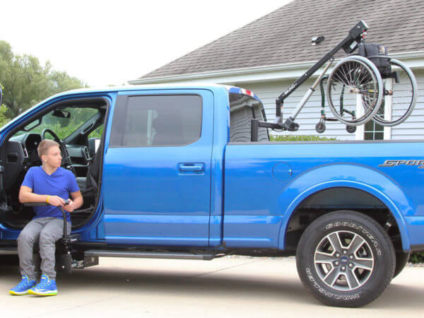 Young Man in transfer seat of blue pickup truck looking at wheelchair attached to Out Rider lift hoisted up over back bed of pickup truck