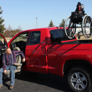 man in turning seat in red pickup truck with out-rider hoist lift in back of truck bed