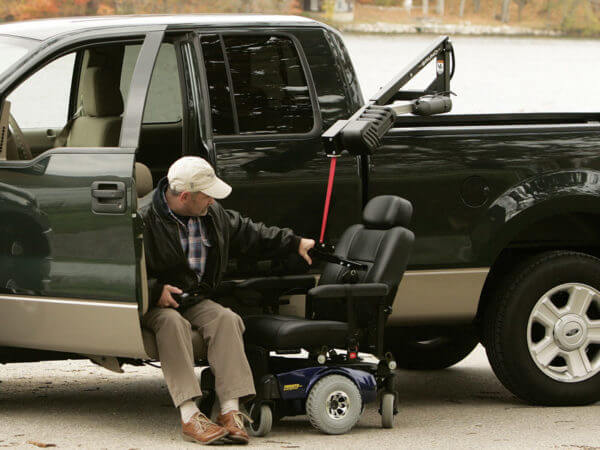 Man in turn-out transfer seat securing Out Rider lift in back bed of pickup truck to power wheelchair