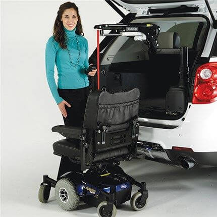 Woman standing next to power wheelchair using bruno lift on back of white vehicle